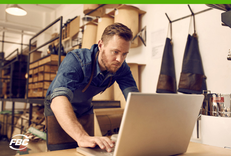 business owner working on laptop in workshop