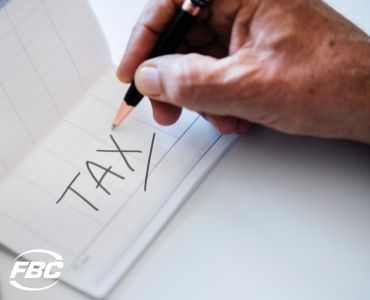 a hand writing the word TAX on a piece of paper