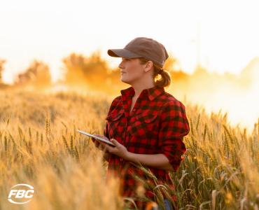 a female farmer gazes into a field