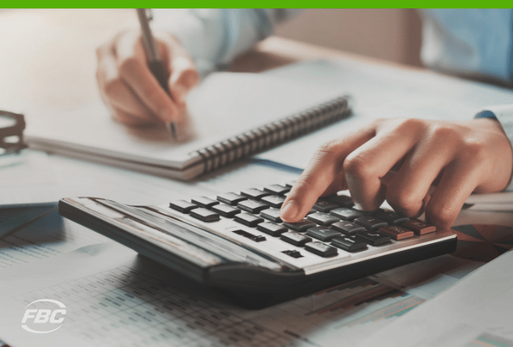 Working at desk with calculator - cash flow