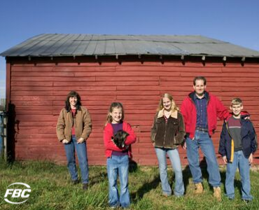 a farm family stands in front of their barn
