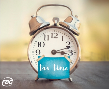 """a clock with a sticker that says """"tax time"""" on it"""