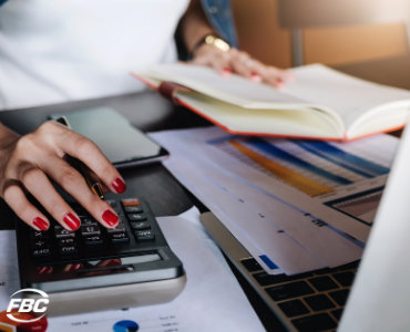 a woman uses a calculator while handling her own bookkeeping